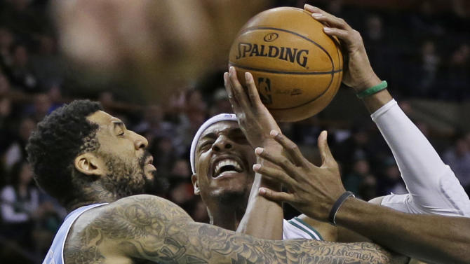 Boston Celtics forward Paul Pierce, right, goes to the hoop against Denver Nuggets guard Wilson Chandler, left, during the first half of an NBA basketball game in Boston, Sunday, Feb. 10, 2013. (AP Photo/Elise Amendola)