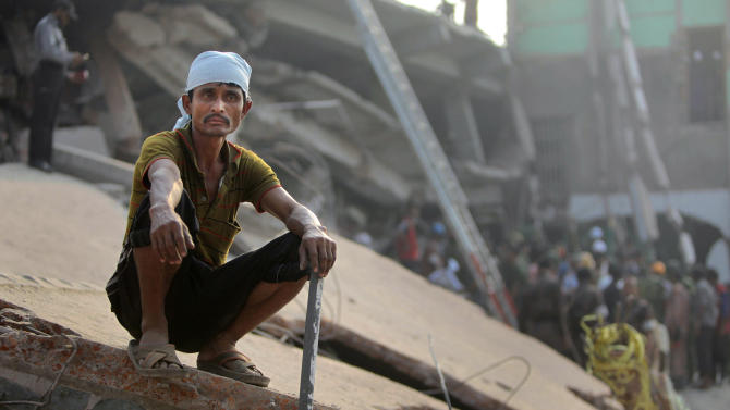 A Bangladeshi rescue worker takes a break at the site of a building that collapsed Wednesday in Savar, near Dhaka, Bangladesh,Thursday, April 25, 2013. By Thursday, the death toll reached at least 194 people as rescuers continued to search for injured and missing, after a huge section of an eight-story building that housed several garment factories splintered into a pile of concrete.  (AP Photo/A.M.Ahad)