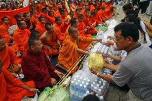 Supporters of CNRP offer food to Buddhist monks during the last day of protest at Freedom Park in Phnom Penh