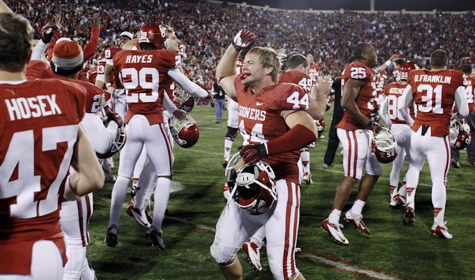 Oklahoma players celebrate following a 51-48 overtime victory over Oklahoma State in an NCAA college football game in Norman, Okla., Saturday, Nov. 24, 2012. Oklahoma linebacker Jaydan Bird (44) is at center. (AP Photo/Sue Ogrocki)