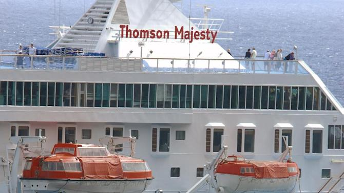 An orange rescue boat docks by a capsized lifeboat from the British-operated cruise ship Thomson Majesty in Santa Cruz port of the Canary Island of La Palma, Spain, Sunday Feb. 10, 2013. A lifeboat from the Thomson Majesty fell into the sea at port in Spain's Canary Islands, killing five people and injuring three others Sunday, officials said. Rescue personnel were called to the dockside after a lifeboat with occupants had fallen overboard from a cruise ship. Spanish national broadcaster RTVE said an emergency training drill was taking place at the time of the accident. (AP Photo/Manuel Gonzalez)