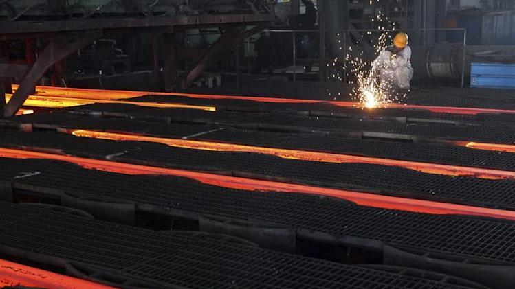 A worker cuts crude steel on a production line at a steel factory in Ganyu