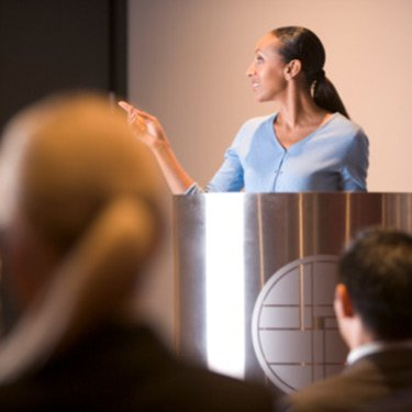 Businesswoman-giving-presentation-at-podium_web