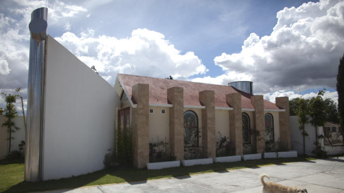 A dog walks near a tomb that was allegedly built by Heriberto Lazcano Lazcano, alleged leader of the Zetas, at a cemetery in the neighborhood of Tezontle in Pachuca, Mexico, Tuesday, Oct. 9, 2012. The tomb is a copy of an actual church in Tezontle, which at one point had a plaque naming Lazcano as the donor. Mexico's Navy says fingerprints confirm that cartel leader Lazcano, an army special forces deserter, was killed Sunday, Oct. 7, 2012 in a firefight with marines in the northern state of Coahuila on the border with the Texas. (AP Photo/Alexandre Meneghini)
