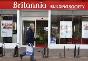 A pedestrian walks past the Britannia Building Society in Northampton, central England