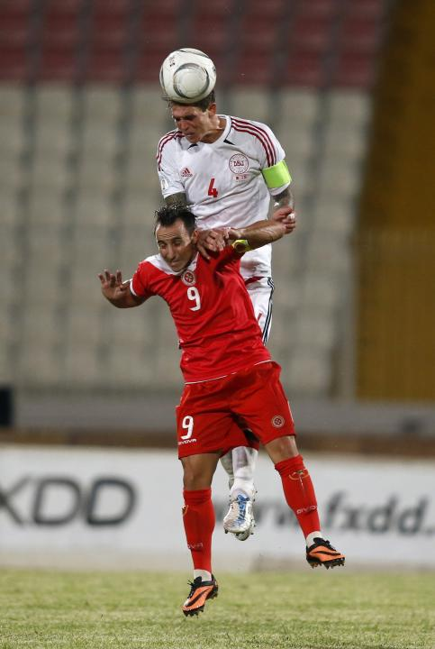Malta's Mifsud and Denmark's Agger jump for a high ball during their 2014 World Cup qualifying soccer match at the National Stadium in Ta' Qali, outside Valletta