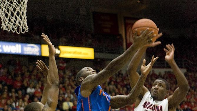 Florida's Kenny Boynton (1) tries to shoot over the defense of Arizona's  Solomon Hill (44) and Mark Lyons (2) during the first half of an NCAA college basketball game at McKale Center in Tucson, Ariz., Saturday, Dec. 15, 2012. (AP Photo/Wily Low)