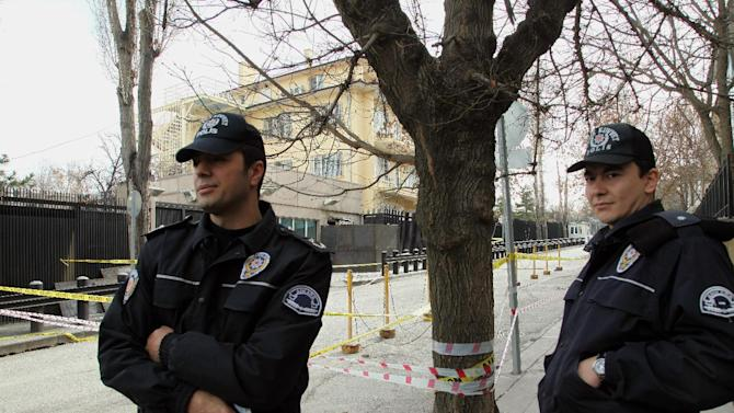 Turkish police officers stand near the side entrance of the U. S. embassy, closed with metal sheeting, rear-center, three days after a suicide bomber attack, in Ankara, Turkey, Monday, Feb. 4, 2013. The suicide bomber who struck the U.S. Embassy in Ankara spent five years in prison on terrorism charges but was released after being diagnosed with a hunger strike-related brain disorder, officials said Saturday. The bomber, identified as 40-year-old leftist militant Ecevit Sanli, killed himself and a Turkish security guard on Friday, in what U.S. officials said was a terrorist attack.(AP Photo/Burhan Ozbilici)