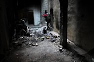 An opposition fighter patrols through an abandoned building in the Jubaila neighbourhood of Syria's northeastern city of Deir Ezzor on October 22, 2013