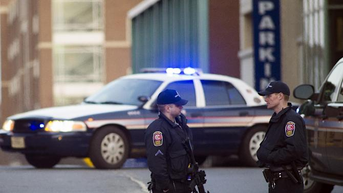 Fairfax County, Va. Police stand guard at Inova Fairfax Hospital Center in Falls Church, Va., Tuesday, March 31, 2015, where a prisoner broke free from his security guard and took his gun. One shot was fired early Tuesday as a guard wrestled with a prisoner, who then fled a northern Virginia hospital with a gun setting off a lockdown and search, police said. (AP Photo/Cliff Owen)