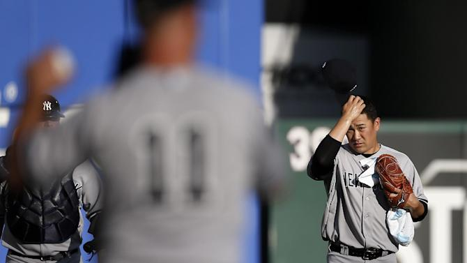 New York Yankees' Brett Gardner, foreground, warms up as New York Yankees' Masahiro Tanaka, of Japan, walks to the dugout from the bullpen before a baseball game against the Texas Rangers, Wednesday, July 29, 2015, in Arlington, Texas. (AP Photo/Tony Gutierrez)