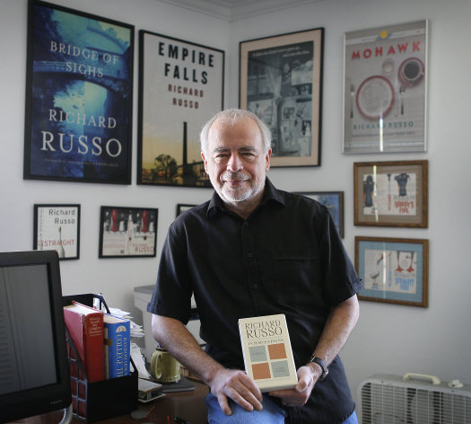 In this photo made Thursday, June 14, 2012, Pulitzer Prize-winning novelist Richard Russo poses with his newest work, &quot;Interventions,&quot; at his home in Camden, Maine. A critic of e-books, Russo wont allow &quot;Interventions&quot; to be sold in electronic form. (AP Photo/Robert F. Bukaty)
