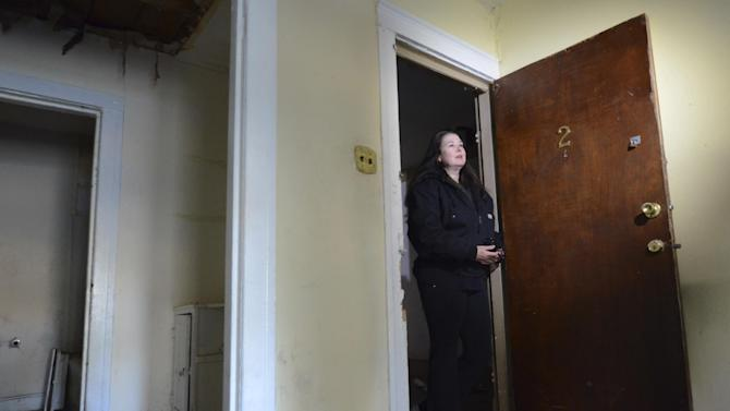 Jane Bryant stands in the doorway of the apartment where Lee Harvey Oswald lived from November 1962 to March 1963 in Dallas, Thursday, Nov. 29, 2012. The apartment complex in the Oak Cliff area is in the process of being demolished. Bryant is under a court order to raze the structure.  (AP Photo/Benny Snyder)