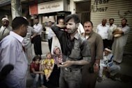 The survivor of a strike by Syrian regime forces arrives at a hospital in the Sheikh Fares district of the northern city of Aleppo. Syrian troops shelled several districts in Aleppo and clashed with rebels on Tuesday, as Damascus ally Iran proposed a simultaneous halt to the violence and a peaceful solution to the conflict