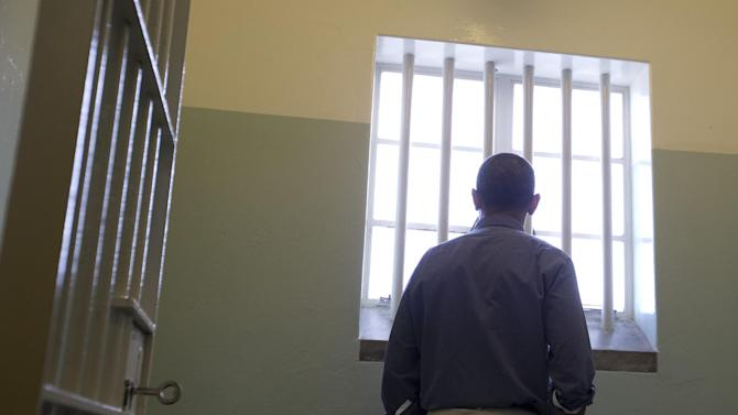RETRANSMISSION TO CORRECT SPELLING OF PRESIDENT'S FIRST NAME - U.S. President Barack Obama U.S. peers out from Section B, prison cell No. 5, on Robben Island, South Africa, Sunday, June 30, 2013. This was former South African president Nelson Mandela's cell, where spent 18 years of his 27-year prison term on the island locked up by the former apartheid government. (AP Photo/Carolyn Kaster)