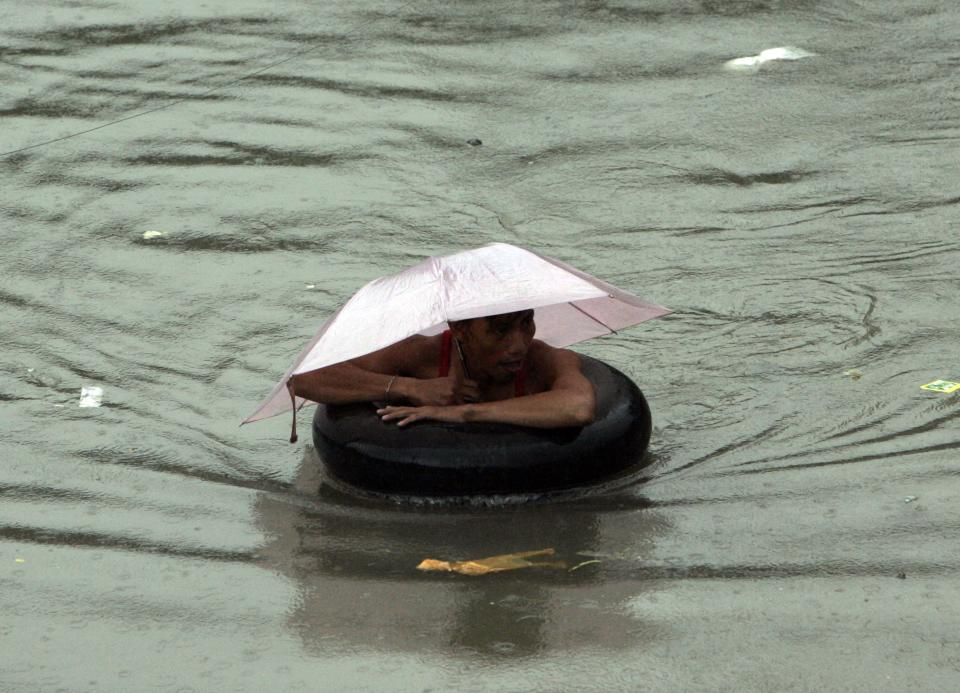 A man uses a floater as he negotiates a chest-deep flood water Tuesday, Aug. 2, 2011 in suburban Quezon City, north of Manila, Philippines. A powerful typhoon is blowing away from the northern Philippines after killing at least four people even though it did not make landfall. (AP Photo/Pat Roque)