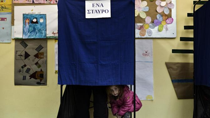 A girl looks out a voting booth at a polling station in Athens