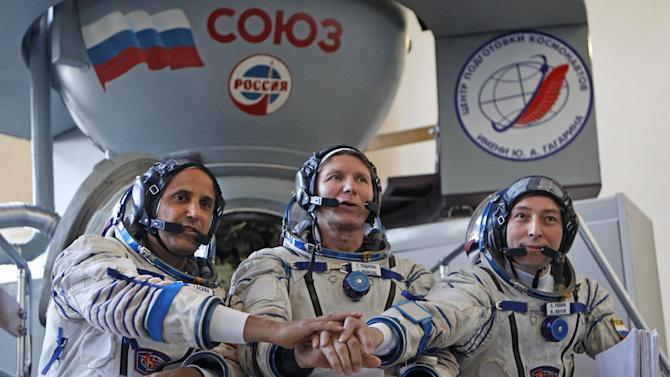 Members of the next expedition to the International Space Station, U.S. astronaut Joseph Acaba, left, and Russian cosmonauts Genady Padalka, center, and Sergey Revin, right, shake hands before their final preflight practical examination in a mock-up of a Soyuz TMA space craft at Russian Space Training Center in Star City outside Moscow, Russia, Tuesday, April 24, 2012. The three are the next crew scheduled to blast off to the International Space Station from Baikonur cosmodrom on a Russian made Souyz TMA-04M space craft on May 15. (AP Photo/Mikhail Metzel)