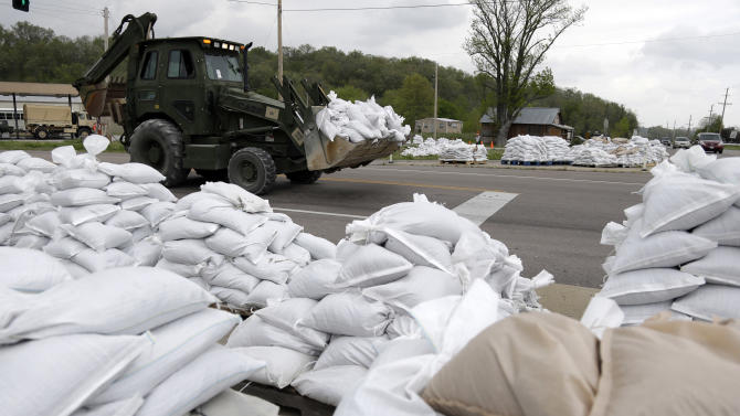 FILE - In this Tuesday, April 23, 2013 file photo, heavy machinery moves sandbags as other sit staged, ready for possible use in the fight against floodwaters in Dutchtown, Mo. The Mississippi River is expected to crest about 10 feet above flood stage Thursday at Dutchtown. The 100 or so residents in the southeast Missouri town have been seeking to have their homes bought out by the Federal Emergency Management Agency. But FEMA says Dutchtown has yet to supply an adequate cost-to-benefit analysis. (AP Photo/Jeff Roberson, File)