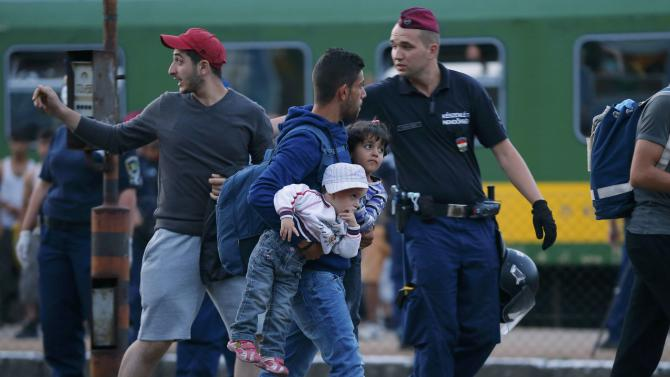 Migrant holding children is escorted from train by police officer at station in Bicske