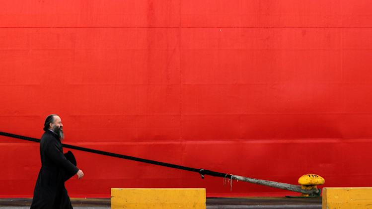 A Greek orthodox priest walks next a docked ship during a strike at Piraeus, the port of Athens, on Wednesday, Sept. 26 2012. A nationwide general strike in debt-crippled Greece against planned new austerity measures shut down schools, banks and government offices, and stopped ferry and train services for 24 hours. Labor unions were planning protest marches in central Athens later Wednesday. (AP Photo/Petros Giannakouris)