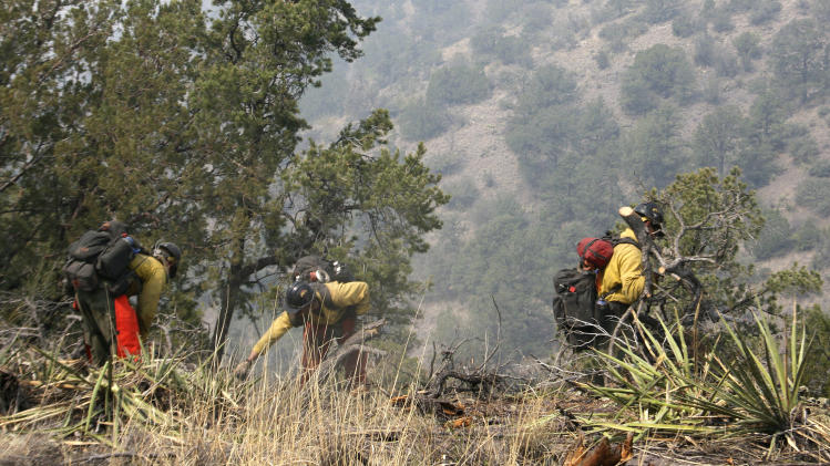 Firefighters from the Granite Mountain Hotshots of Prescott, Ariz., cut a fire line along a mountain ridge outside Mogollon, N.M., on Saturday, June 2, 2012. The crew is part of an effort to manage and contain the Whitewater-Baldy fire which has burned more than 354 square miles of the Gila National Forest in New Mexico.  (AP Photo/U.S. Forest Service, Tara Ross)