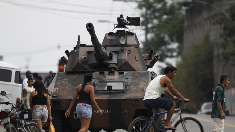 Residents walk past an armored vehicle during an operation against alleged drug traffickers at the Complexo do Alemao slum in Rio de Janeiro, Brazil, Saturday, Nov. 27, 2010. Occasional gunfire broke the tense stillness Saturday morning as armored vehicles prepared to push past barriers into Rio's most dangerous slum, as police increased pressure on drug traffickers believed to have ordered the wave of violence that has terrorized the city this week. (AP Photo/Felipe Dana)