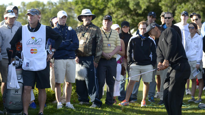 Tiger Woods, right, hits out of the rough off the 12th fairway as caddie Joe LaCava, second from left, watches during the first round of the Arnold Palmer Invitational golf tournament in Orlando, Fla., Thursday, March 21, 2013.(AP Photo/Phelan M. Ebenhack)