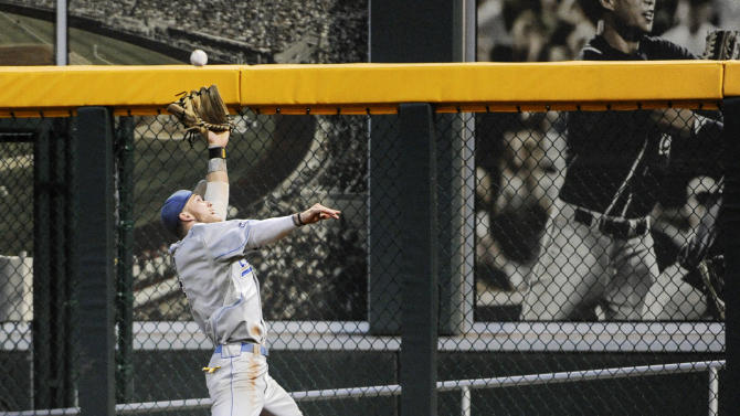 UCLA right fielder Eric Filia makes a leaping catch of a fly ball hit by Mississippi State's Nick Ammirati in the fifth inning of Game 1 in their NCAA College World Series baseball finals, Monday, June 24, 2013, in Omaha, Neb. (AP Photo/Francis Gardler)