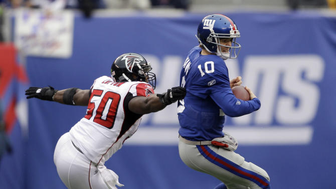 New York Giants quarterback Eli Manning (10) evades a tackle by Atlanta Falcons middle linebacker Curtis Lofton (50) during the first half of an NFL wild card playoff football game Sunday, Jan. 8, 2012, in East Rutherford, N.J. (AP Photo/Matt Slocum)
