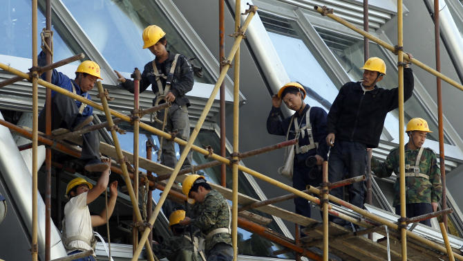 FILE - In this May 30, 2012 file photo, workers stand on the scaffolding of a modern commercial building in Beijing, China. Plagued by uncertainty and fresh setbacks, the world economy has weakened further and will grow more slowly over the next year, the International Monetary Fund says in its latest forecast. Advanced economies are risking recession, the international lending organization said Tuesday, Oct. 9 in a quarterly update of its World Economic Outlook, and the malaise is spreading to more dynamic emerging economies such as China. (AP Photo/Ng Han Guan, File)