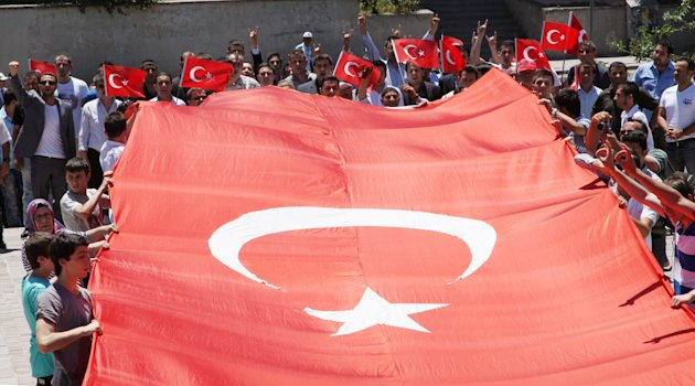 Turks hold a national flag as they march in Ankara, Turkey to protest the killings of soldiers , Wednesday, June 20, 2012, a day after Kurdish rebels attacked Turkish military units with mortars and rocket-propelled grenades in the Daglica area of Hakkari province which borders northern Iraq Kurdish areas in southeastern Turkey, sparking clashes that killed eight soldiers and 18 rebels.(AP Photo/Burhan Ozbilici)
