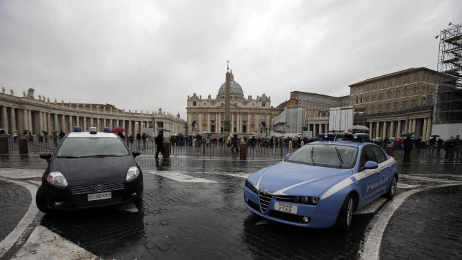 Italian police, left, and carabinieri cars are parked outside St. Peter's Square, at the V atican, Saturday, Feb. 23, 2013 As 100.000 pilgrims are expected to crowd St. Peter's Square for the last Angelus prayer of Pope Benedict XVI on Sunday morning, the Rome municipality is expected to increase by more then 30% the law enforcement agents, volunteers and transportation, while more then 2000 cctv security cameras will monitor the Roman territory with dozens aiming only at the areas surrounding the Vatican. (AP Photo/Gregorio Borgia)