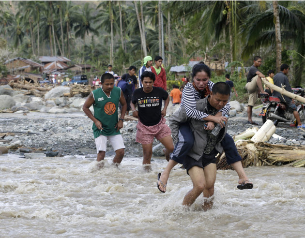 Residents cross a river in the flash flood-hit village of Andap, New Bataan township, Compostela Valley in southern Philippines Wednesday, Dec. 5, 2012.  Typhoon Bopha, one of the strongest typhoons t