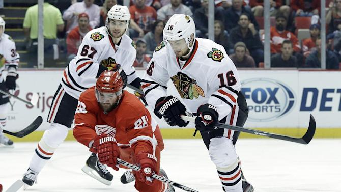 Detroit Red Wings defenseman Carlo Colaiacovo (28) tries to clear the puck from Chicago Blackhawks center Marcus Kruger (16), of Sweden, during the first period in Game 6 of the Western Conference semifinals in the NHL hockey Stanley Cup playoffs in Detroit, Monday, May 27, 2013. (AP Photo/Paul Sancya)