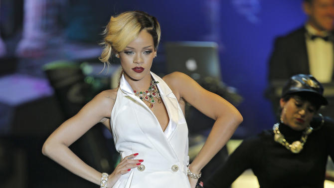 """FILE - In this Wednesday, July 10, 2013 file photo, singer, songwriter Rihanna performs at """"Le Sporting"""" in Monaco during her """"Diamonds World Tour"""". A British judge has ruled Wednesday July 31, 2013, in favor of the singer Rihanna, who sued retailer Topshop for selling a T-shirt bearing her image without permission. High Court Justice Colin Birss says buyers were likely deceived into buying the shirt under the belief she had authorized its sale. (AP Photo/Lionel Cironneau, File)"""