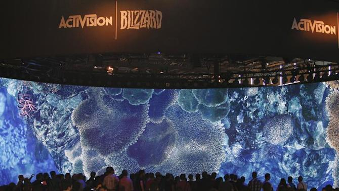 Visitors look at a presentation at the ActiVision Blizzard exhibition stand during the Gamescom 2013 fair in Cologne