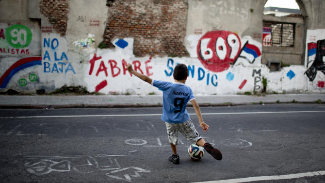 A boy wearing a soccer jersey associated with Uruguayan striker Luis Suarez, winds up to kick a soccer ball at a wall blanketed with electoral propaganda promoting the ruling party, Broad Front, in Montevideo, Uruguay Friday, Oct. 24, 2014. The political party of outgoing President Jose Mujica, who gained international renown for social reforms such as legalization of marijuana and gay marriage, leads going into Sunday's election to replace him but victory is far from assured. (AP Photo/Natacha Pisarenko)