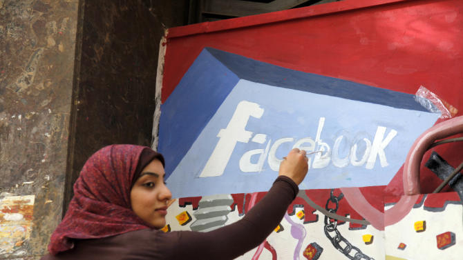 """FILE - In this March 30, 2011, file photo. an art student from the University of Helwan paints the Facebook logo on a mural commemorating the revolution that overthrew Hosni Mubarak in the Zamalek neighborhood of Cairo, Egypt. The team from the CIA's Open Source Center, housed in a unassuming brick building in a Virginia industrial park, pores daily over tweets, Facebook, newspapers, TV news channels, local radio stations, Internet chat rooms _ anything overseas that anyone can access, and contribute to, openly. The center saw the uprising in Egypt coming said the center's director, Doug Naquin. The center already had """"predicted that social media in places like Egypt could be a game-changer and a threat to the regime,"""" he said in a recent interview with The Associated Press. (AP Photo/Manoocher Deghati, File)"""