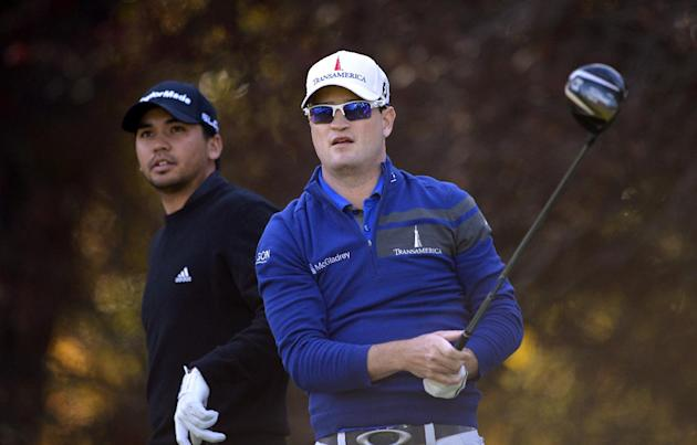 Zach Johnson, right, tees off on the second hole as Jason Day, of Australia, watches during the first round of the Northwestern Mutual World Challenge golf tournament at Sherwood Country Club, Thursda