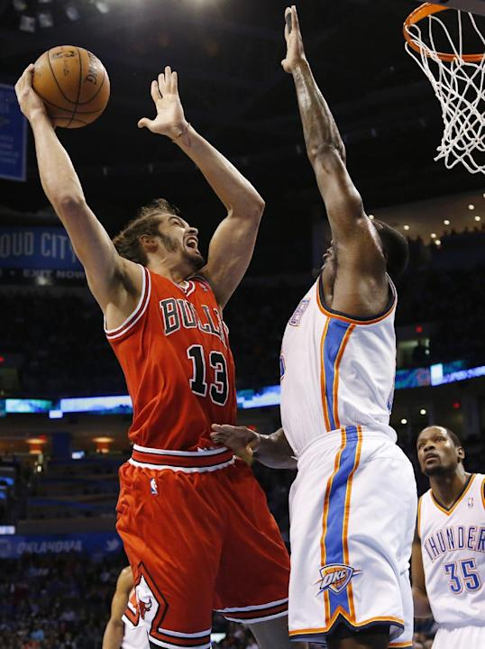 Chicago Bulls center Joakim Noah (13) shoots in front of Oklahoma City Thunder center Kendrick Perkins during the first quarter of an NBA basketball game in Oklahoma City, Thursday, Dec. 19, 2013. Okl