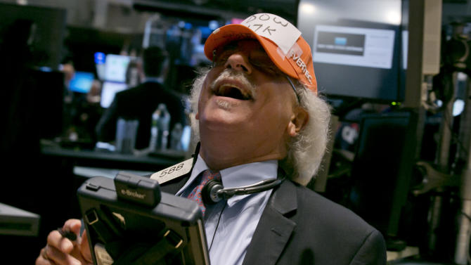 """FILE - In this Tuesday, July 1, 2014, file photo, trader Peter Tuchman jokes with a handmade """"Dow 17,000"""" cap as he works on the floor of the New York Stock Exchange. Five full years after a devastating recession officially ended, the economy is finally showing the vigor that Americans have long awaited. In June 2014, employers added 288,000 jobs, reducing the unemployment rate to 6.1 percent, the lowest since September 2008. (AP Photo/Richard Drew, File)"""
