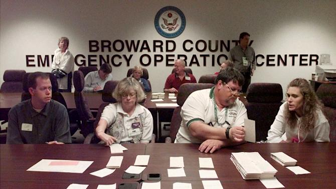 FILE - This Nov. 19, 2000 file photo shows counters and observers continuing a hand recount of Broward County ballots at the Broward Emergency Operation Center in Plantation, Fla. Ever hear about national elections where the winners aren't known for days as government officials count votes and double-check results? Thank goodness we don't have to wait that long for election results in the U.S., right? Not so fast. In the US, most states don't announce official election results until weeks after Election Day. Florida is scheduled to certify its results Nov. 20 _ two weeks after the polls close. Ohio's deadline is Nov. 27. (AP Photo/Amy E. Conn, File)