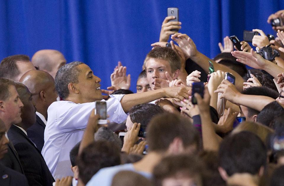 President Barack Obama reaches out to students and parents at Washington-Lee High School in Arlington, Va., after speaking about his efforts to prevent interest rates from doubling on federal student loans, Friday, May 4, 2012. (AP Photo/J. Scott Applewhite)