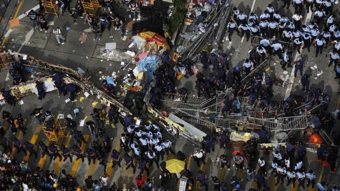 Police take control of the barricades set up by pro-democracy protesters before demolishing them at a protest site on the main Nathan Road at Mongkok district in Hong Kong