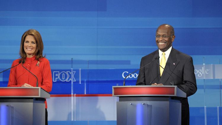 Republican presidential candidate Rep. Michele Bachmann, R-Minn, left, listens as businessman Herman Cain makes a statement during a Fox News/Google debate Thursday, Sept. 22, 2011, in Orlando, Fla. (AP Photo/Phelan M. Ebenhack, Pool)