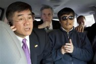 Handout photo from the U.S. Embassy Beijing Press office shows U.S. Ambassador to China Gary Locke talking on a mobile phone as he accompanies blind activist Chen Guangcheng in a car, in Beijing