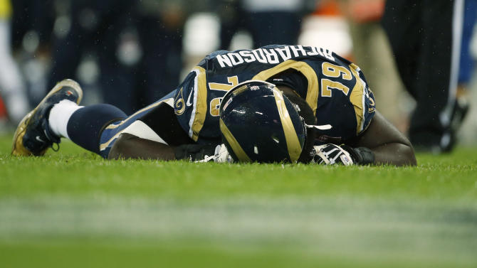 St. Louis Rams tackle Barry Richardson, lays on the pitch after a hard tackle during the second half of a NFL football game at Wembley Stadium, London, Sunday, Oct. 28, 2012. (AP Photo/Matt Dunham)