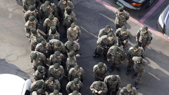 South Korean soldiers wait for their colleagues after casting their absentee votes for the presidential election at a local polling station in Seoul, South Korea, Thursday, Dec. 13, 2012. South Korea's presidential election is scheduled for Dec. 19. (AP Photo/Lee Jin-man)