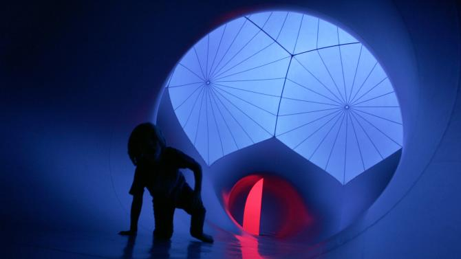 A child crawls on the floor of Exxopolis, an inflatable walk-in luminarium at Grand Park in Los Angeles, California